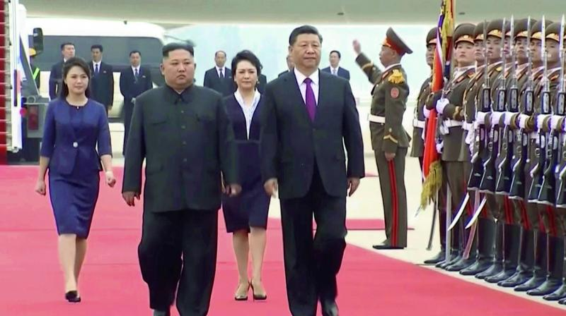 North Korean leader Kim Jong Un and Chinese President Xi Jinping, walk together on Xi's arrival at an airport in Pyongyang, North Korea on Thursday.