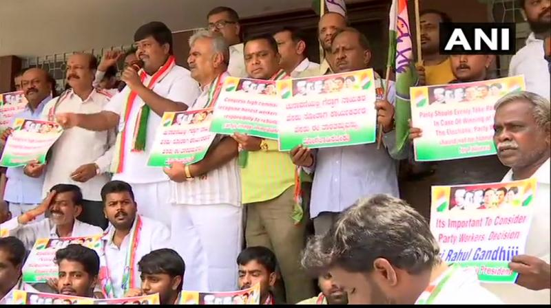 Congress workers demonstrate outside party office urging Rahul Gandhi to continue as Congress President in Bengaluru. (Photo: ANI)