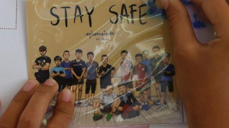 A Thai well wisher puts a poster to pray for boys and their soccer coach who had been trapped since June 23, in Mae Sai, Chiang Rai province, northern Thailand. (Photo: AP)