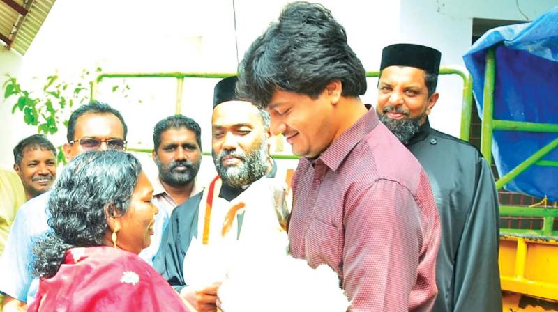 Alappuzha sub-collector V.R. Krishna Teja hands over a Lamb to a beneficiary at a function held in Haripad. (DC)