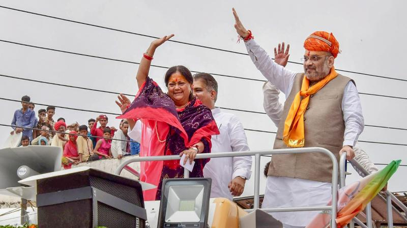 BJP President Amit Shah with Rajasthan Chief Minister Vasundhara Raje wave at their supporters during a public meeting.