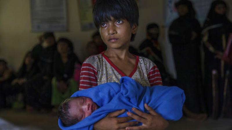 Rohingya Muslim girl Afeefa Bebi holds her few-hours-old brother as doctors check her mother Yasmeen Ara at a community hospital in Kutupalong refugee camp. (Photo: PTI)