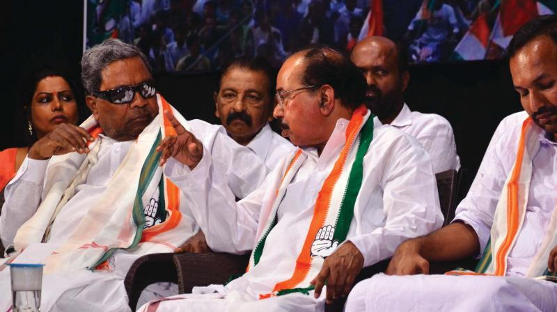 Senior Congress leader Siddaramaiah in conversation with former chief minister M. Veerappa Moily at a party workers' meeting in Mangaluru on Saturday.  (Photo:  KPN)