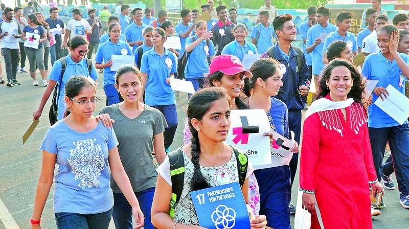 Youngsters participate in a walkathon on the eve of International Women's Day, on the Beach Road in Visakhapatnam on Wednesday. (Photo: DC)