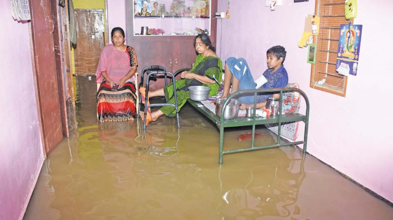 Rainwater entered into a house at Kambar Nagar in Pudukkottai town and the inmates of the house sit on the cot and the chair, on Saturday.(DC)