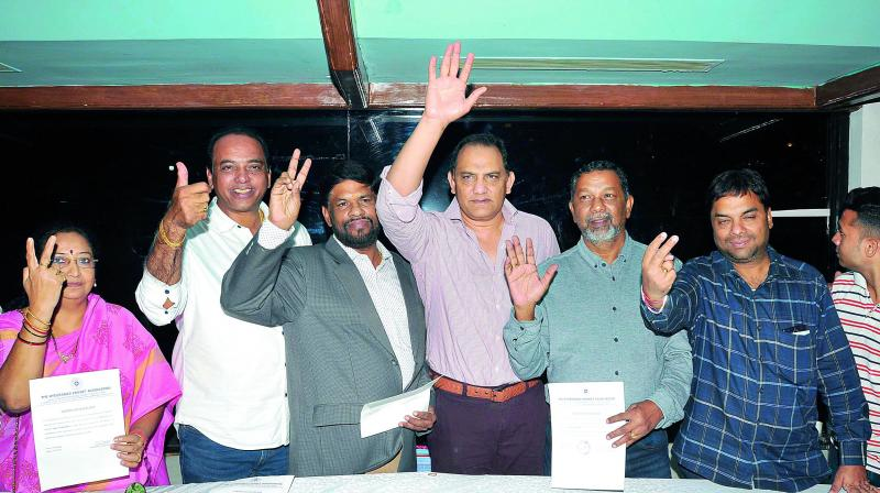 President Mohammad Azharuddin (third from right) waves after winning the Hyderabad Cricket Association elections along with his panel members — councillor P. Anuradha (left), joint secretary Naresh Sharma (second from left), secretary R. Vijayanand (third from left), vice-president K. John Manoj (second from right) and treasurer Surender Agarwal (right) at the RGICS on Friday.