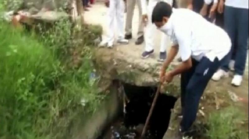 Rampur DM Anjaneya Kumar Singh engaged in cleaning a drain. (Photo: ANI)