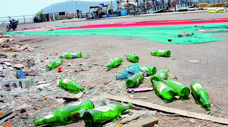 Liquor bottles scattered at the Vizag harbour on Monday. (Deccan chronicle)