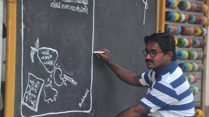 Bukhari busy drawing cartoons on the entrance of his house at Peruvallur in Tirurangadi.