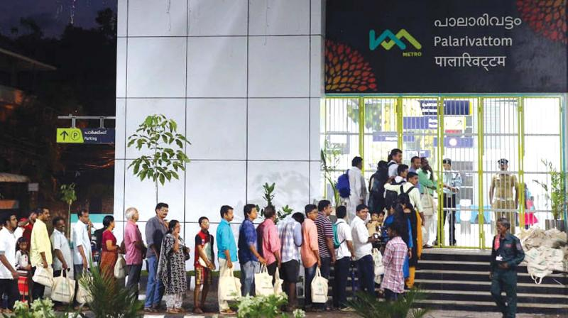 People queue up in front of Palarivattom Metro rail station in the small hours as the facility began commercial operations on Monday. (Photo: Arunchandra Bose)