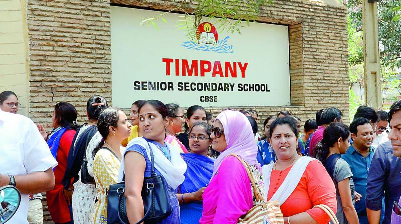 Parents gather in front of the Timpany Senior Secondary School after news of the new fee structure broke.