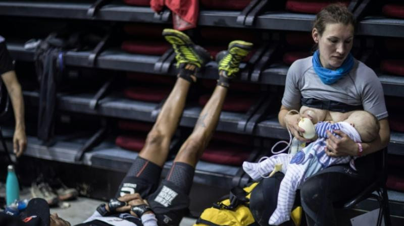 Great-Britain's trail runner Sophie Power breastfeeds her three months old baby Cormac. (Photo: AFP)