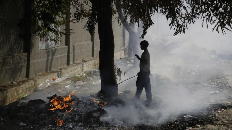 A boy stands next to burning garbage on the outskirts of New Delh on Tuesday. (Photo: AP)