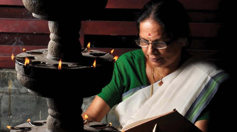 A woman reads the Ramayana at home during Karkidakam. (file pic)