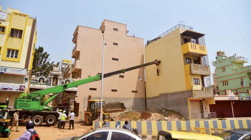 A crane being used on Wednesday to straighten a three-storeyed house that had begun to tilt at Horamavu in Bengaluru from Sunday