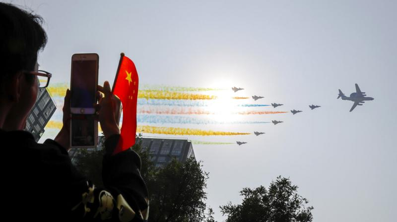 A man uses his smartphone to film Chinese military planes trail colored smoke as they fly in formation past the sun during a parade to commemorate the 70th anniversary of the founding of Communist China in Beijing, on Tuesday, October 1, 2019. (Photo: AP)