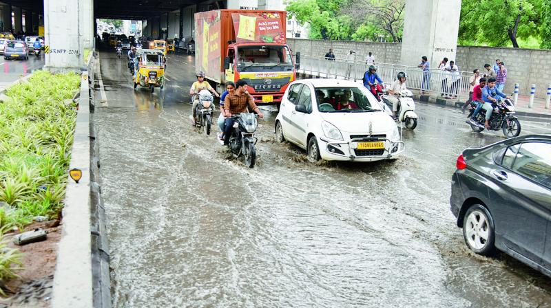 Commuters wade through the waterlogged road under the Ameerpet Metro station.  (Photo:S. Surender Reddy)
