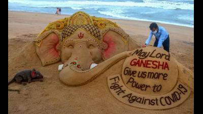 Sand artist Sudarsan Pattnaik creates a sand sculpture on the occasion of Ganesh Chaturthi with message