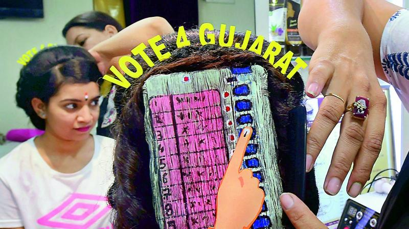 A girl with an EVM painted on her hair campaigns for voting ahead of Gujarat Assembly polls, in Ahmedabad on Thursday. (Photo:  PTI)
