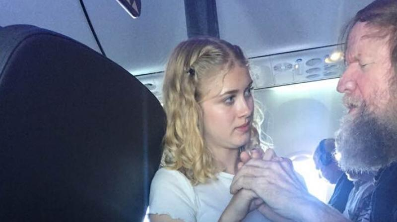 Clara Daly helping out th eblind and deaf man on an Alaska Airlines flight. (Facebook Screengrab/ Lynette Scribner)