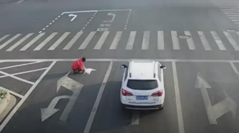 Surveillance footage shows him painting his own arrows at a junction in the eastern city of Lianyungang. (Photo: Youtube/CGTN)