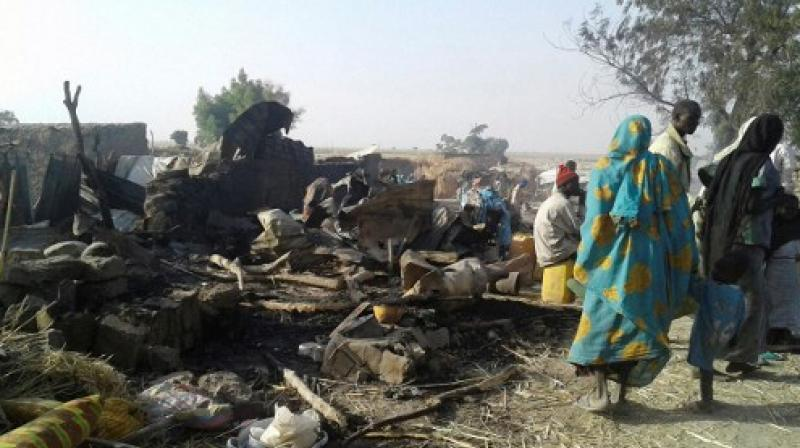 This handout image received courtesy of Doctors Without Border (MSF) shows people standing next to destruction after an air force jet accidentally bombarded a camp for those displaced by Boko Haram Islamists, in Rann, northeast Nigeria. (Photo: AFP)