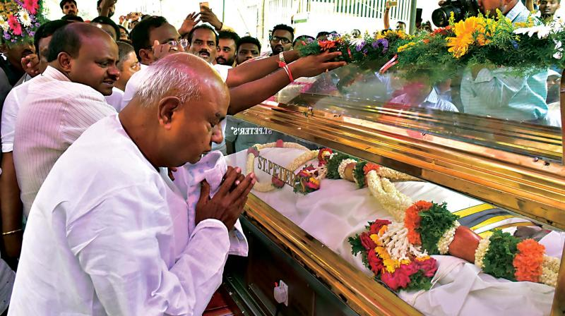JD(S) supremo H.D. Deve Gowda and Chief Minister H.D. Kumaraswamy pay tribute to JD(S) worker K.G. Hanumantharayappa, who was killed in the serial blasts in Sri Lanka, during the last rites at Dasarahalli in Bengaluru on Wednesday (Photo:  KPN)