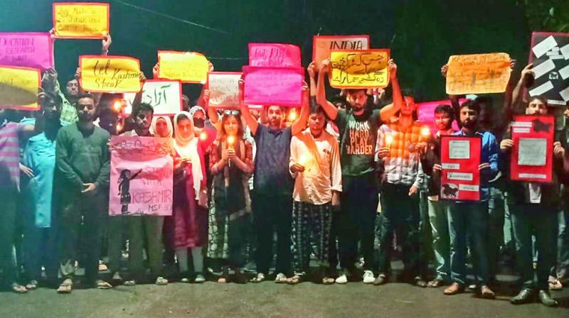 Students of University of Hyderabad hold candles and posters during their protest march on the campus to express their solidarity with Kashmiris who are suffering from lockdown.