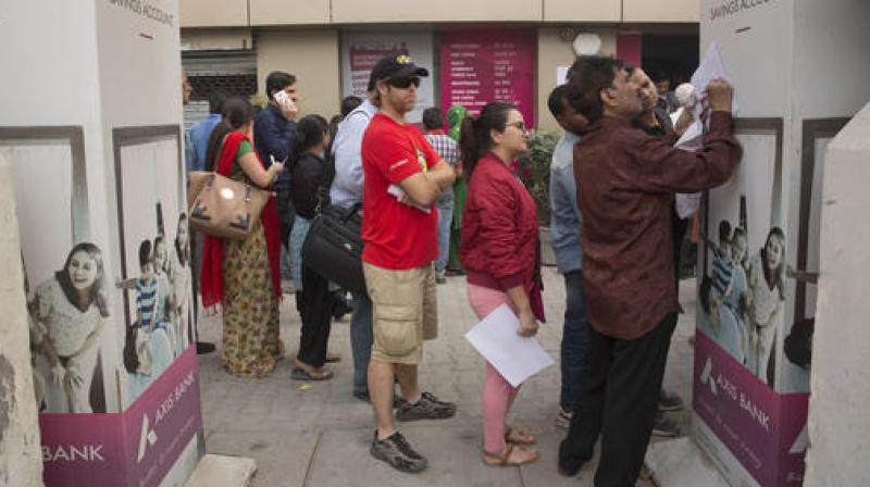 TForeign tourist stand in a queue to exchange discontinued currency notes outside a bank in New Delhi. (Photo: PTI)