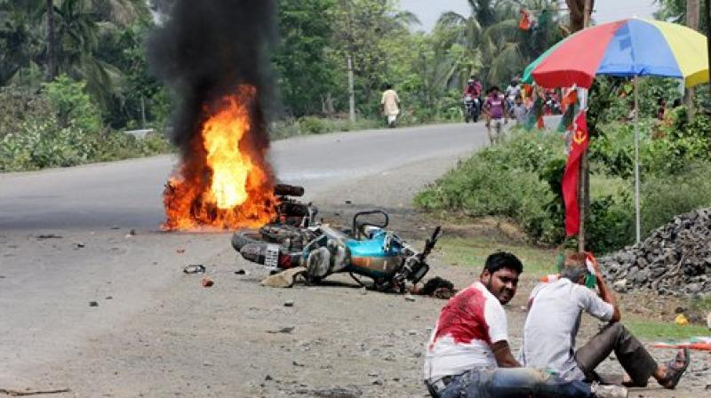 People injured in poll violence sit by the side of a road as a vehicle is set on fire by locals during Panchayat polls, in Nadia district of West Bengal on Monday. (Photo: PTI)