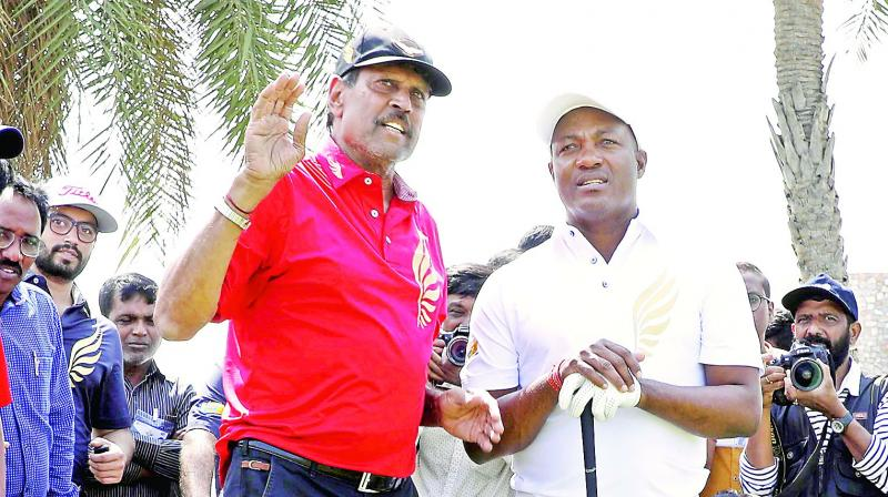 Former cricketers turned golfers Kapil Dev (left) and Brian Lara in action at the Golden Eagles Golf Championship in Hyderabad on Saturday.  (Surendra P.)