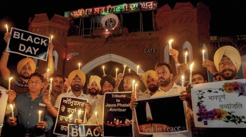 Members of National Human Rights and crime control organisation participate in a candlelight vigil to pay tribute to victims of Amritsar train accident. (Photo: PTI)