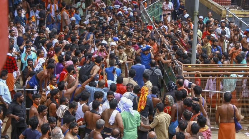 Protestors gather as a Trichy resident who had trekked up with her family to Sabarimala temple, in Pathanamthitta, on Saturday. (Photo: PTI)