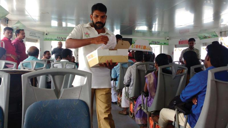 The staff of 'Aditya' distribute sweets to passengers in connection with second anniversary of inception of the boat.