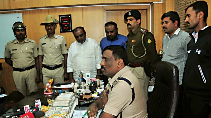Bengaluru city police with the sandalwood racket accused Syed Riyaz  and his son, Sher Ali during a press conference at DCP's office in Cubbon Park in Bengaluru on Saturday  (Image DC)