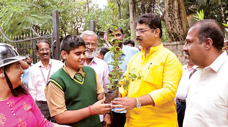 Minister R. Ashok gives a sapling to a schoolboy to mark PM Modi's birthday, in Bengaluru on Tuesday. He said the Centre has reduced Karnataka's  flood damage estimate from Rs 38,485 crore to 35,160 crore (Photo: DC)