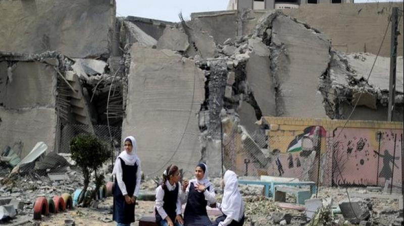 Palestinian students inside their damaged school nearby a building that was destroyed by Israeli airstikes, in Gaza. (Photo: ANI)