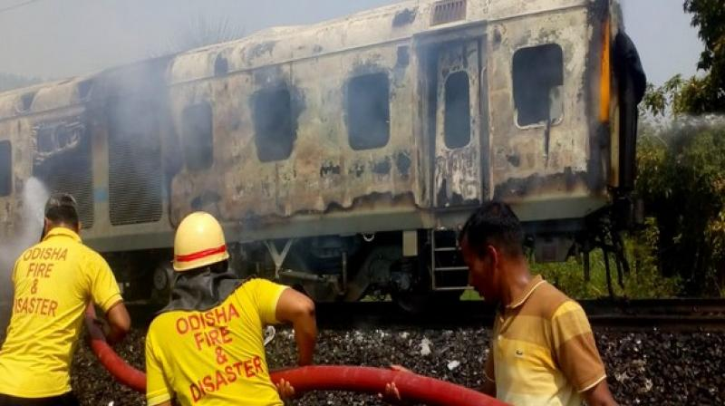 Firefighters from ODFRA tackling fire in the affected New Delhi-Bhubhaneswar Rajdhani express' coach. (Photo: ANI)