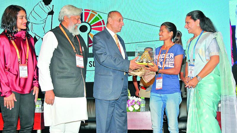 Governor E.S.L. Narasimhan (centre) felicitates mountaineer Malavath Purna with the Telangana Jagruthi Young achievers award at the Telangana Jagruthi International Youth Leadership Conference on Sunday. TRS MP  K. Kavitha (right), wrestler Babita Phogat (left), 'Waterman of India' Dr Rajendra Singh (second from left) are also seen. The Governor stressed on the importance of the youth and gender equality.(Photo: P. Surendra)