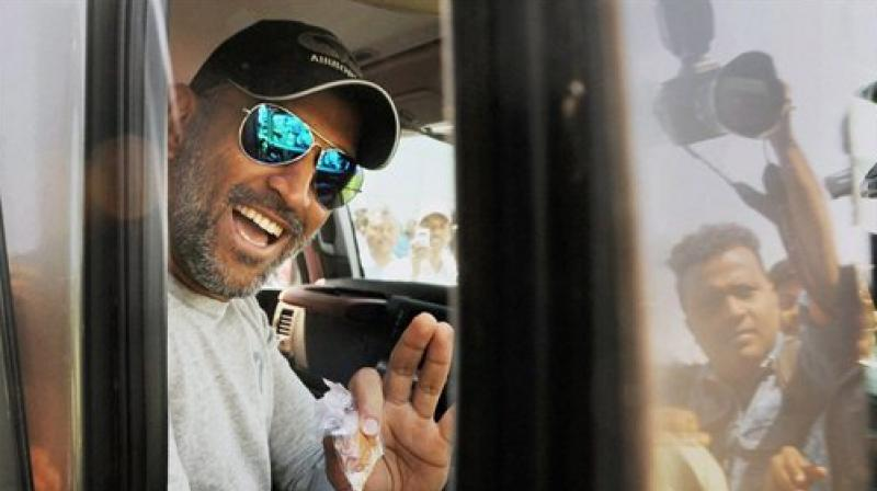MS Dhoni waves at fans from his SUV after being spotted outside Ranchi's Birsa Munda airport. (Photo: PTI)