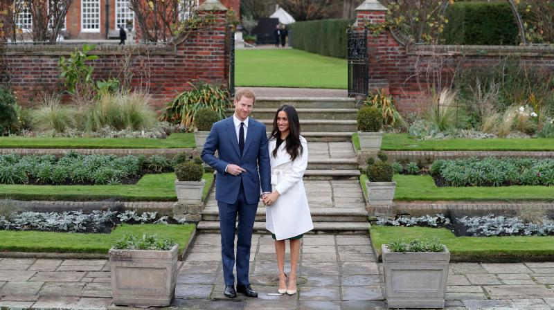 In this file photo taken on November 27, 2017 Britain's Prince Harry and his fiancée US actress Meghan Markle pose for a photograph in the Sunken Garden at Kensington Palace in west London on November 27, 2017. (Photo: AFP)