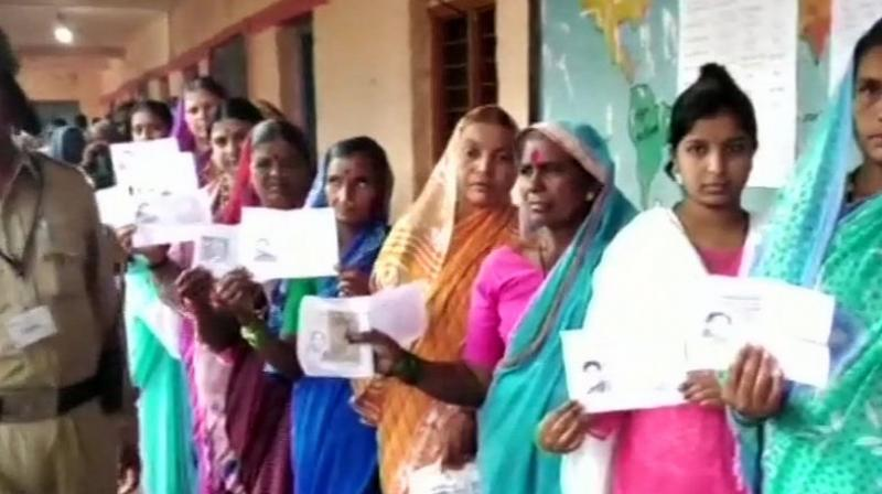 Women queue up outside booth no.50 in Hirepadasalgi village of Jamkhandi to cast their votes. (Photo: ANI/Twitter)