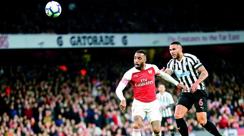 Arsenal's Alexandre Lacazette (left) vies for the ball during the match against Newcastle United in the English Premier League at the Emirates Stadium in London on Monday. Arsenal won 2-0.(Photo: AP)