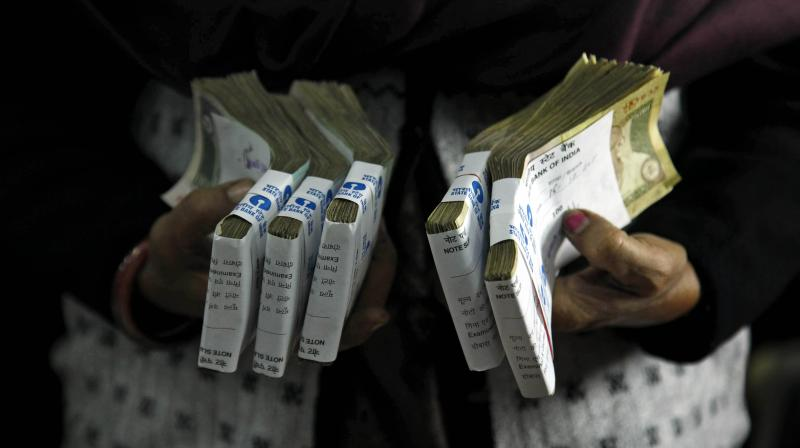 A cashier holds bundles of Indian currency notes at a bank in Allahabad. (Photo: AP)