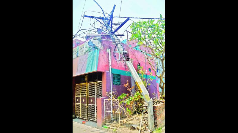 An electricity pole broken in half rests on a house in Odisha's Puri district on Tuesday.