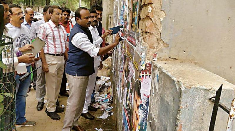 Mayor Sampath Raj tears off posters from a wall as part of the two-day drive to remove flexes, banners and posters across the city, in Bengaluru on Saturday —DC