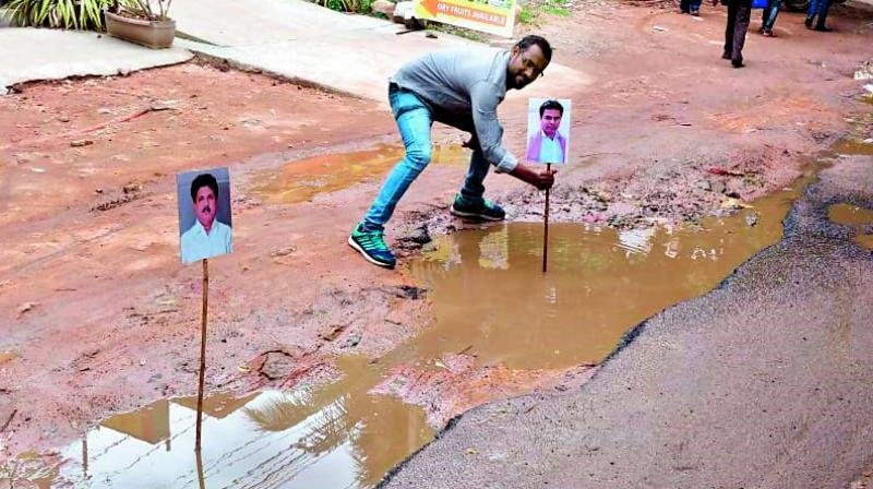 People place photos of minister K.T. Rama Rao and Kukatpally MLA Madhavaram Krishna on top of potholes at KPHB.