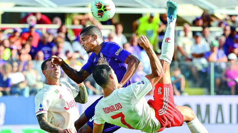 Portuguese forward Cristiano Ronaldo performs an overhead kick despite Fiorentina's Brazilian defender Dalbert during the Italian Serie A football match on Saturday. (Photo: AFP)