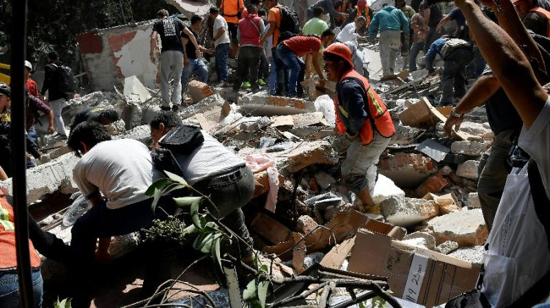 People remove debris of a building which collapsed after a quake rattled Mexico City (Photo: AFP)