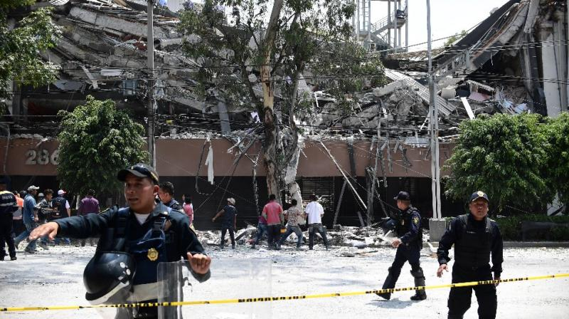 Police officers cordon off the area around a collapsed building in Mexico City (Photo: AFP)